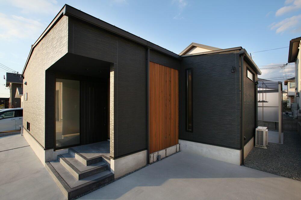 分譲地での計画の為、プライバシーを確保しつつ採光を取る為に中庭を設けたコートハウスにしました。軒の無いシンプルデザインの外観はブラックの外壁材(サイディング)に目隠しで使用した木の格子をアクセントにデザインしました。