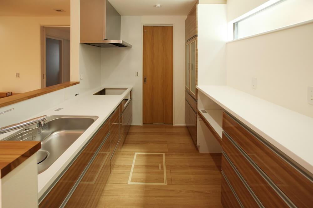 キッチンとカップボードは、見た目が揃って使い勝手も良いメーカー製で統一しました。奥の扉は洗面脱衣室に繋がっていて家事動線も最短な間取りになっています。