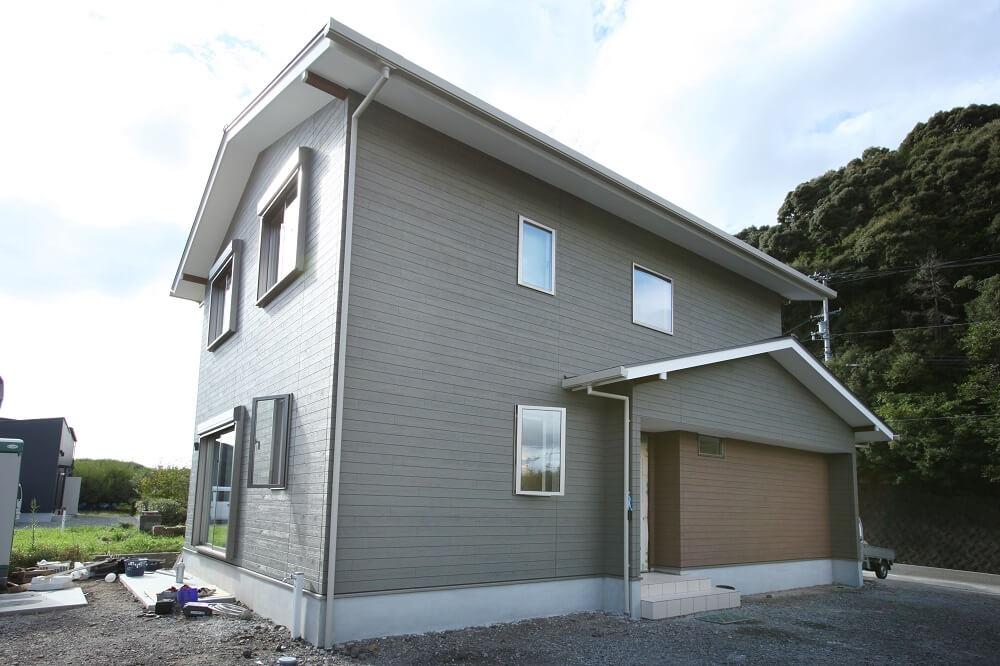 ベースがグリーンの外壁にブラウンの外壁をアクセントにした、三角屋根(切り妻屋)の外観です。