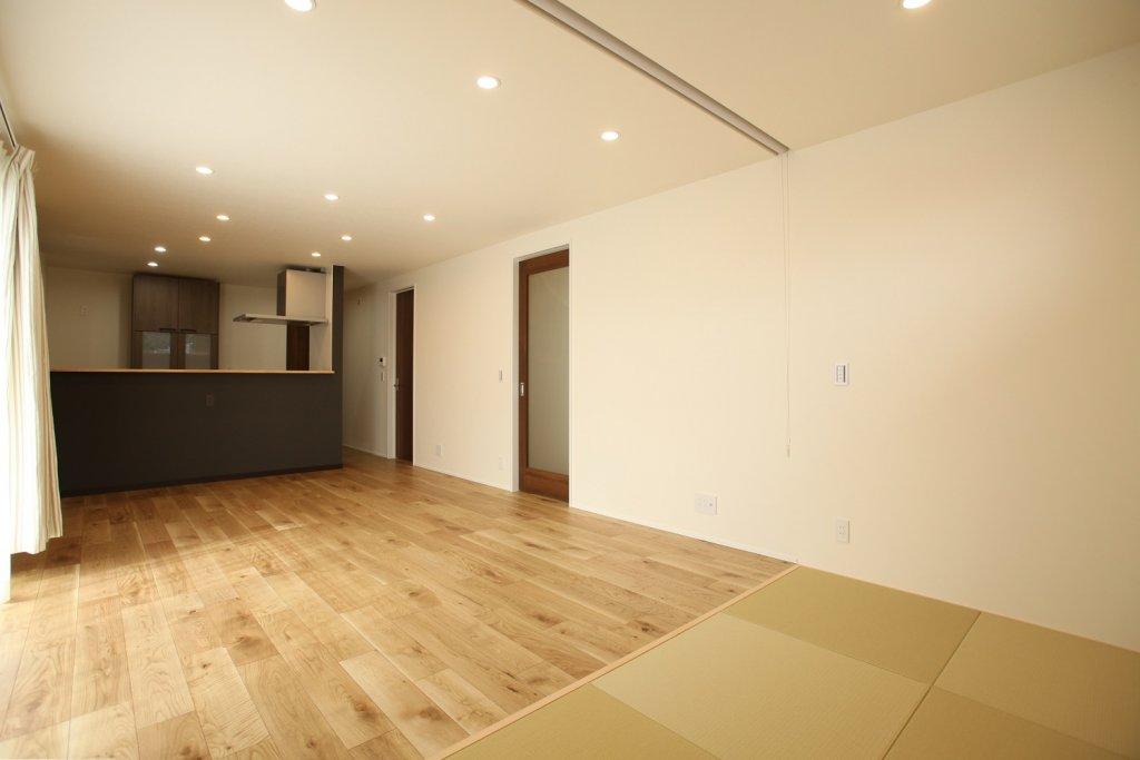 ホワイト×木目×ダーク色でまとめたインテリア。キッチンの前の壁は壁紙をアクセントカラーでブラックとし、床材はマットな風合いのラスティック塗装仕上げのナラ樫の突板フローリングを採用しました。