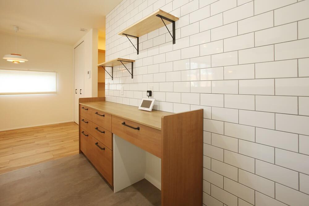 キッチン家電をすぐ使えるようカウンター型にし、壁にはサテリッティの白いタイルをグレー目地でやさしいアクセントとしました。上部にはインテリアを楽しむ棚を付け、日々お気に入りを飾ることを楽しむ場所の一つにしました。