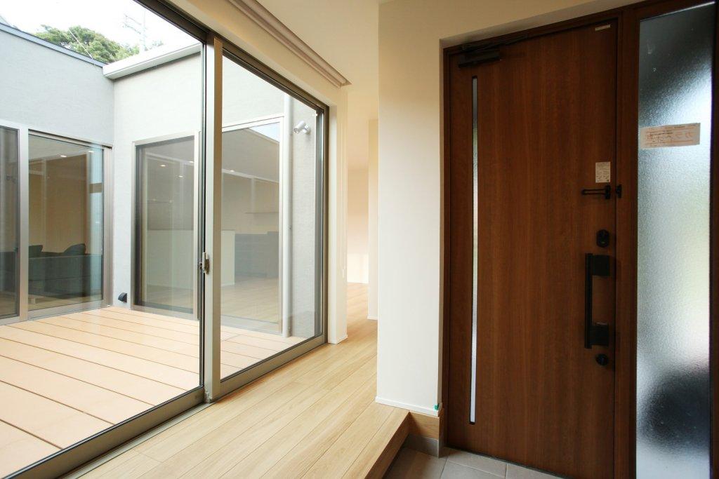 コートハウス(中庭)の大きな掃き出し窓で玄関とリビングがつながるので、行ってきますやただいま、来客の様子もリビングにいながら知ることができます
